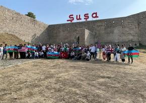 Azerbaijanis living abroad wave tricolor flag on Jidir Plain